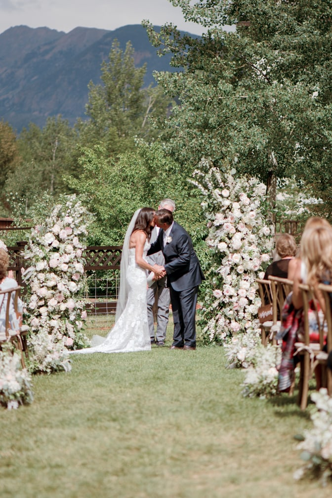 First kiss at ceremony underneath floral arch with mountain backdrop at Larkspur Events and Dining in Vail