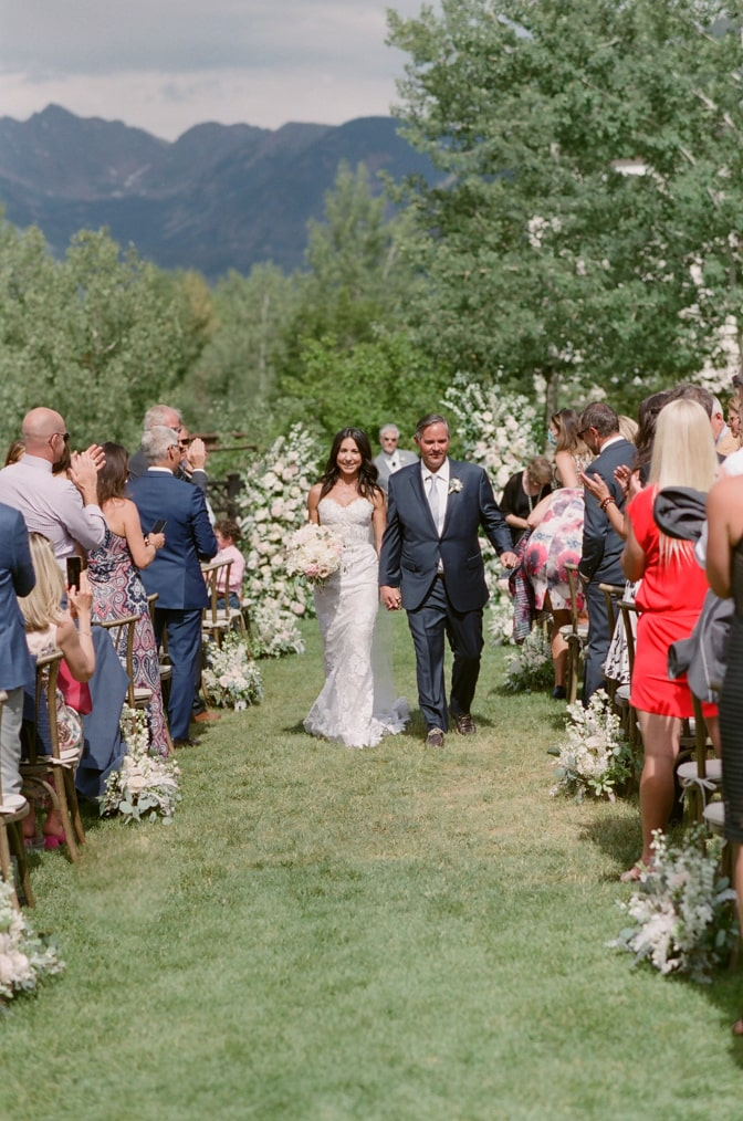 Happy now married couple walking down the aisle at Larkspur in Vail