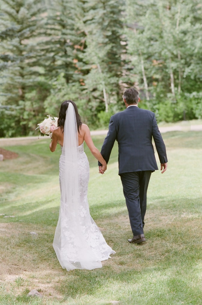 Wedding couple in distance walking on grass with pine trees in front of them at Larkspur Events and Dining in Vail