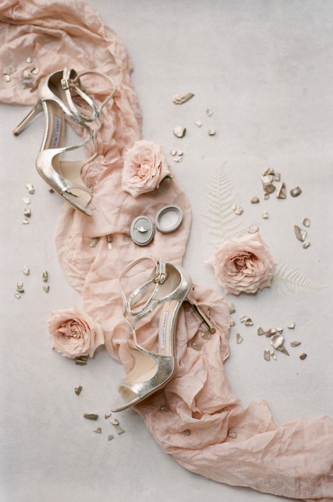 Styled shot of bride's sparkly Jimmy Choo shoes and surrounded decorations