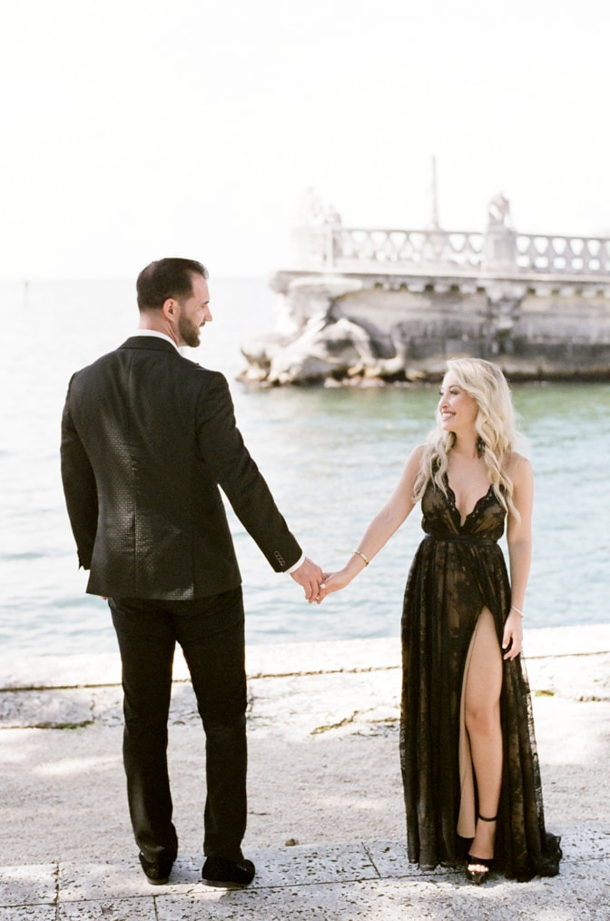 Bride and groom to be holding hands at the seaside of Vizcaya Museum and Gardens in Miami