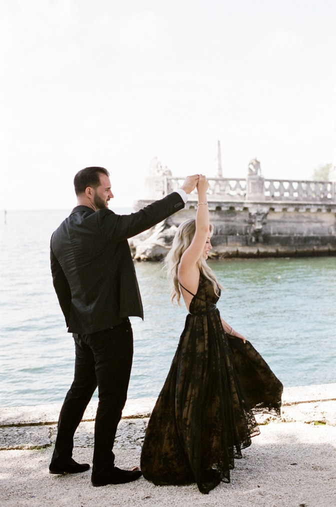 Engaged couple dancing along the seaside of the Vizcaya Museum and Gardens in Miami Florida