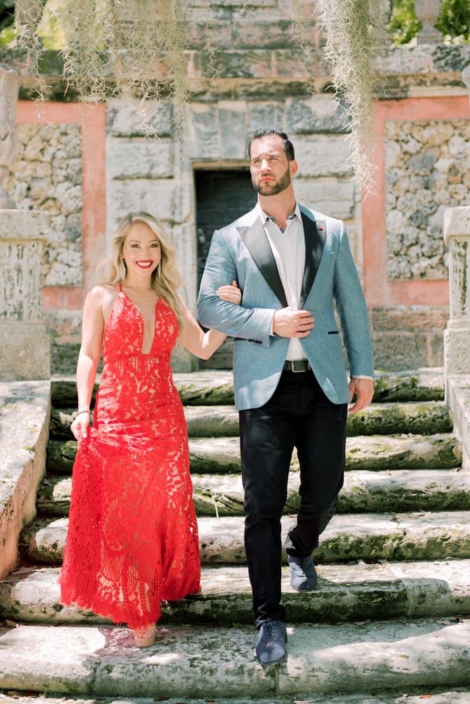 Bride and groom to be walking down the stairs with their fashionable and colorful outfits during their Miami engagement session at the Vizcaya Museum and Gardens