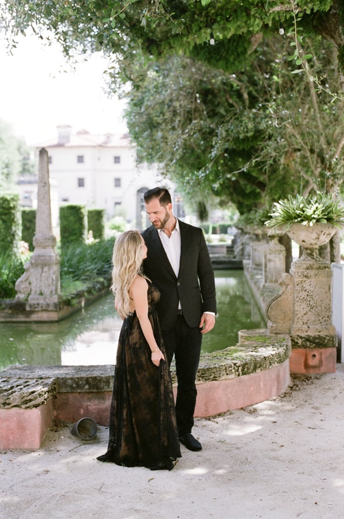 Bride and groom to be looking at each other while walking in the Vizcaya Museum and Gardens in Miami
