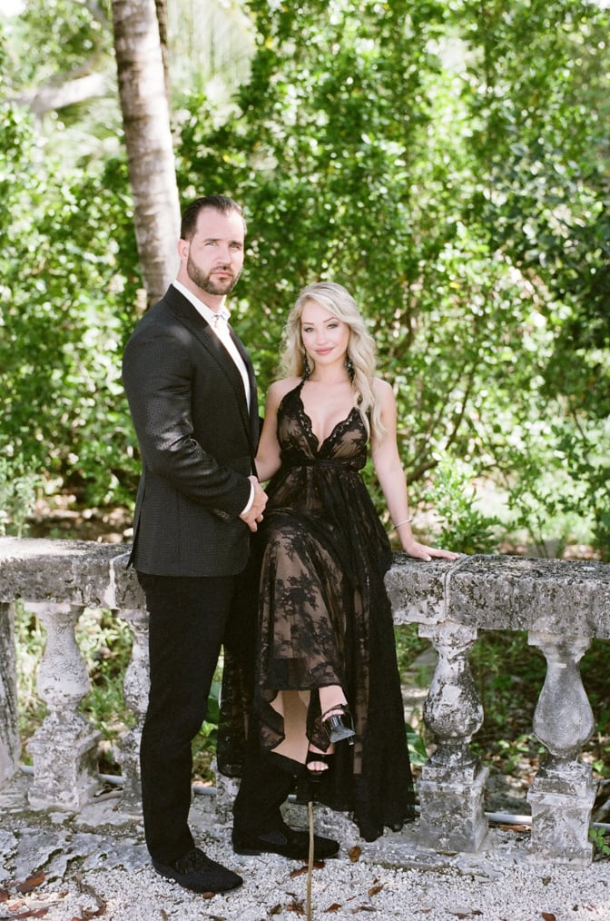 Bride and groom to be wearing fashionable black outfits during their Miami engagement session at Vizcaya Museum and Garden