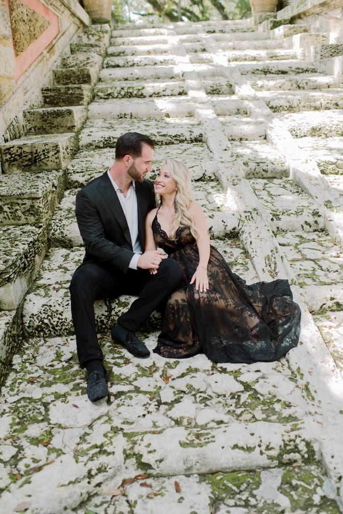 Bride and groom to be in their couture black outfits sitting on the stairs of Vizcaya Museum and Gardens in Miami