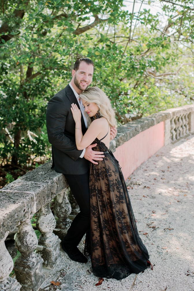 Bride and groom to be embracing each other in their black couture outfits during their Miami engagement session