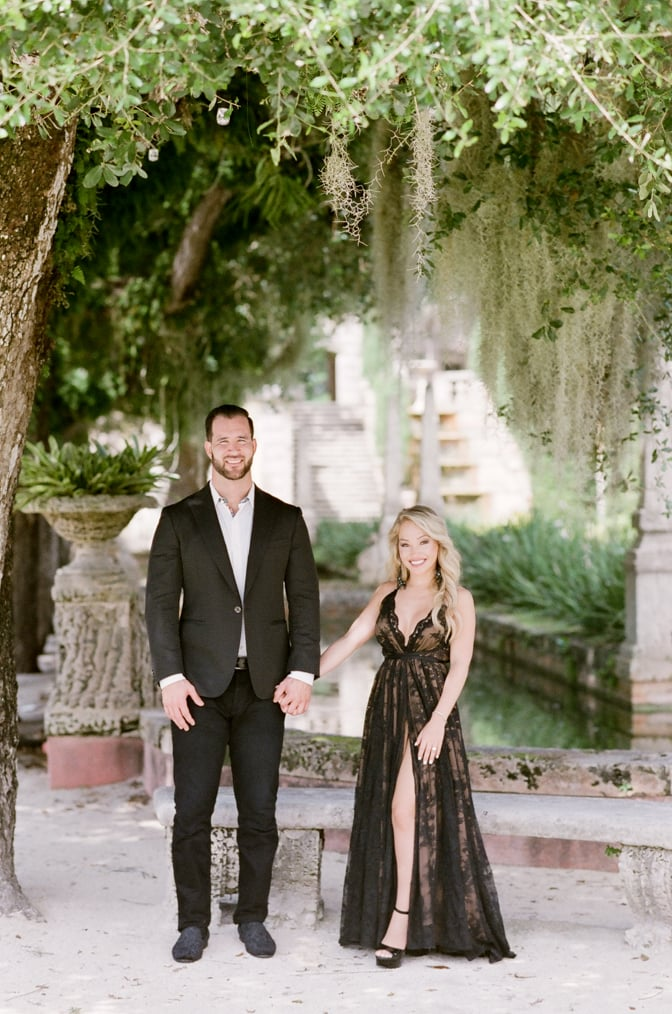 Bride and groom to be holding hands while standing next to each other during their Vizcaya Museum and Gardens engagement session in Miami
