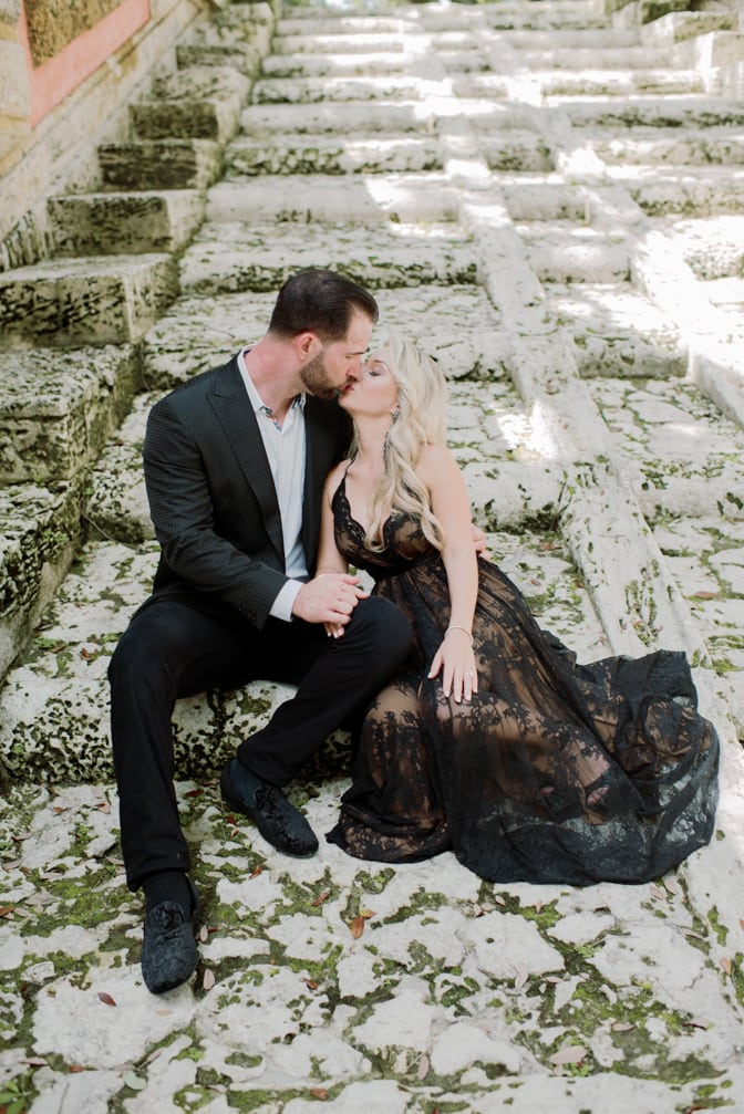 Bride and groom kissing each other on the base of the stairs at Vizcaya Museum and Gardens in Miami