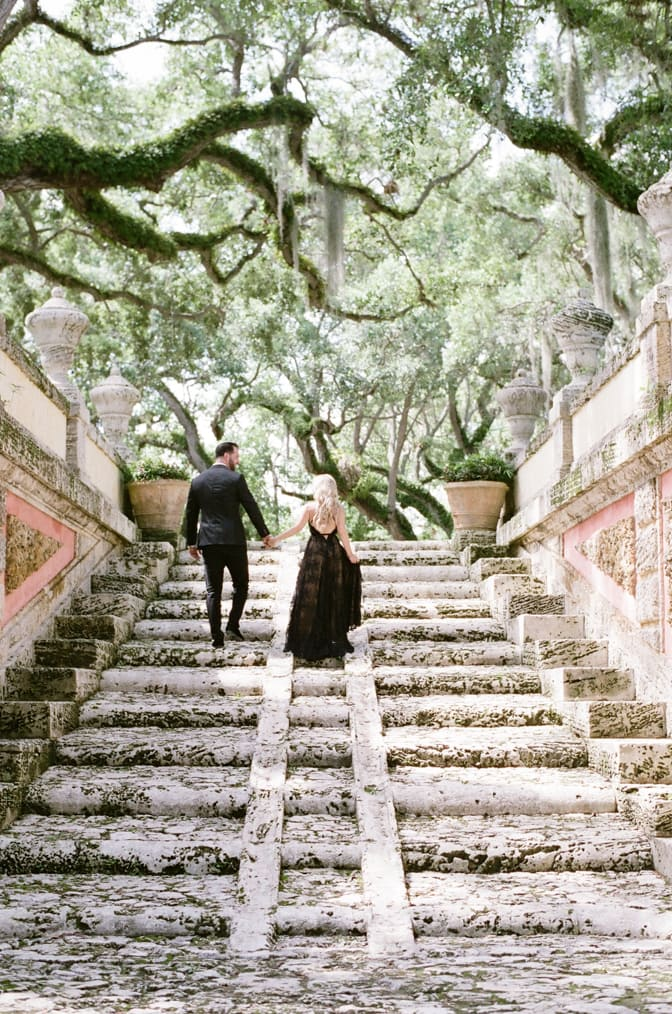 Bride and groom walking up the stairs while holding hands at Vizcaya Museum and Gardens in Miami Florida