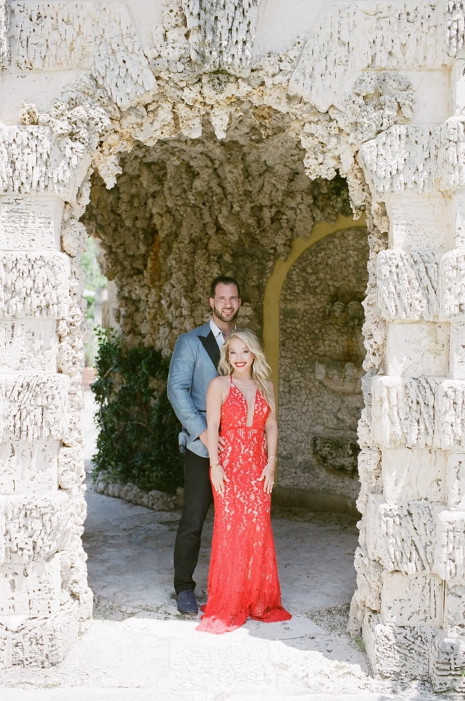 Bride in a red lace dress and groom in a turquoise jacket standing in front of each other in a stone cove at Vizcaya Museum in Miami