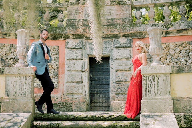 Bride and groom at top of stairs at Vizcaya Museum and Gardens in Miami posing for destination wedding photographer Tamara Gruner
