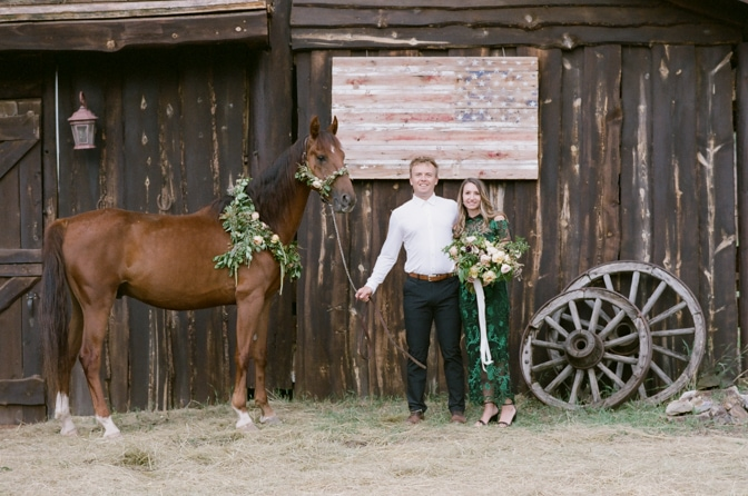 Bride and groom to be holding a brown horse in front of a horse ranch in Colorado Springs