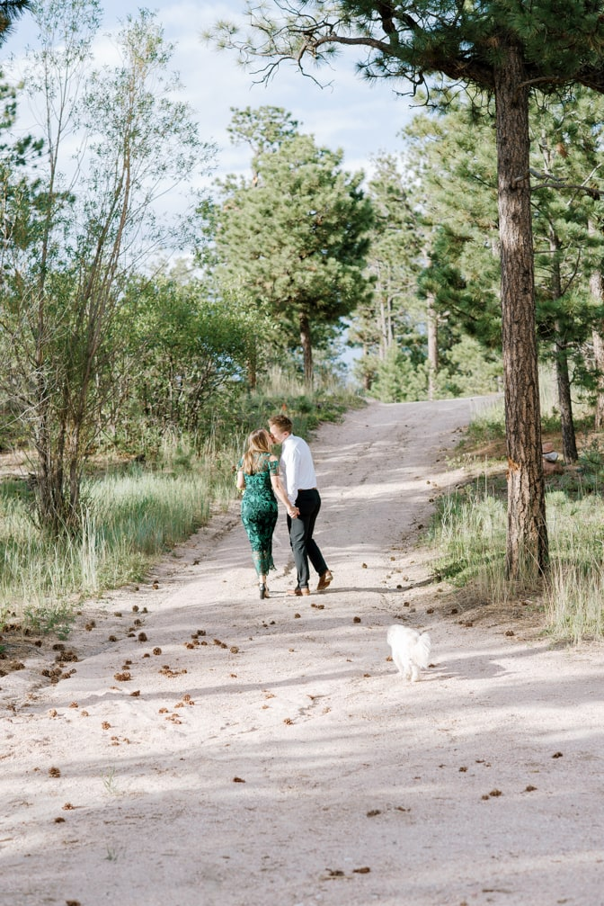 Engaged couple walking and kissing during their Colorado engagement session