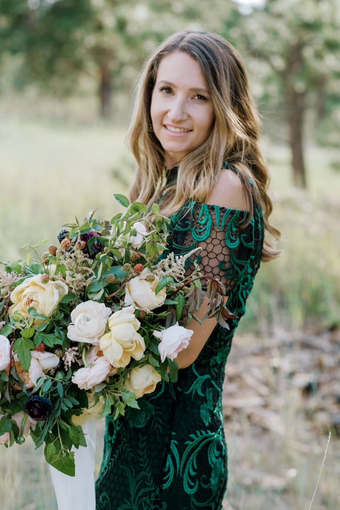 Colorado bride wearing a green lace Marchesa fashion dress and holding a bouquet in her arms