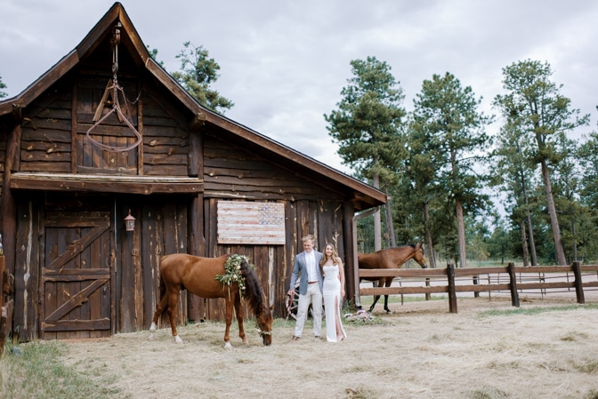 Engaged couple with a horse in front of a ranch in Colorado Springs during their Colorado engagement session