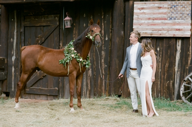 Engaged couple looking at their beautiful horse adorned with a flower wreath during their Colorado engagement