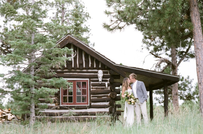 Bride and groom to be kissing in front of a hut in Colorado Springs