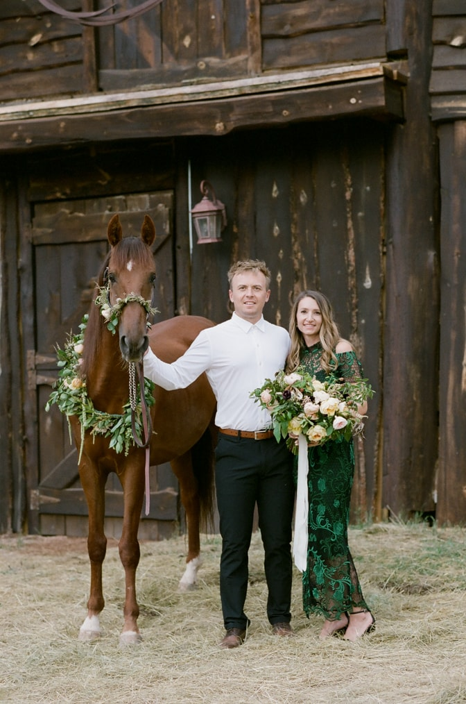 Engaged couple holding a horse adorned with flower wreath in Colorado