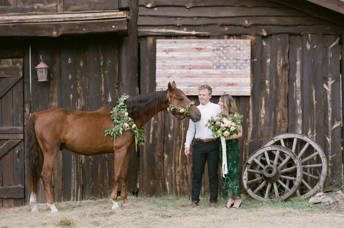 Engaged couple in front of a horse ranch with a brown horse in Colorado