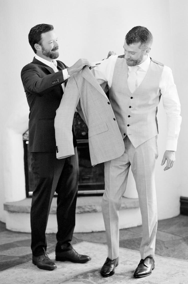 Best man dressing the groom at Colorado wedding