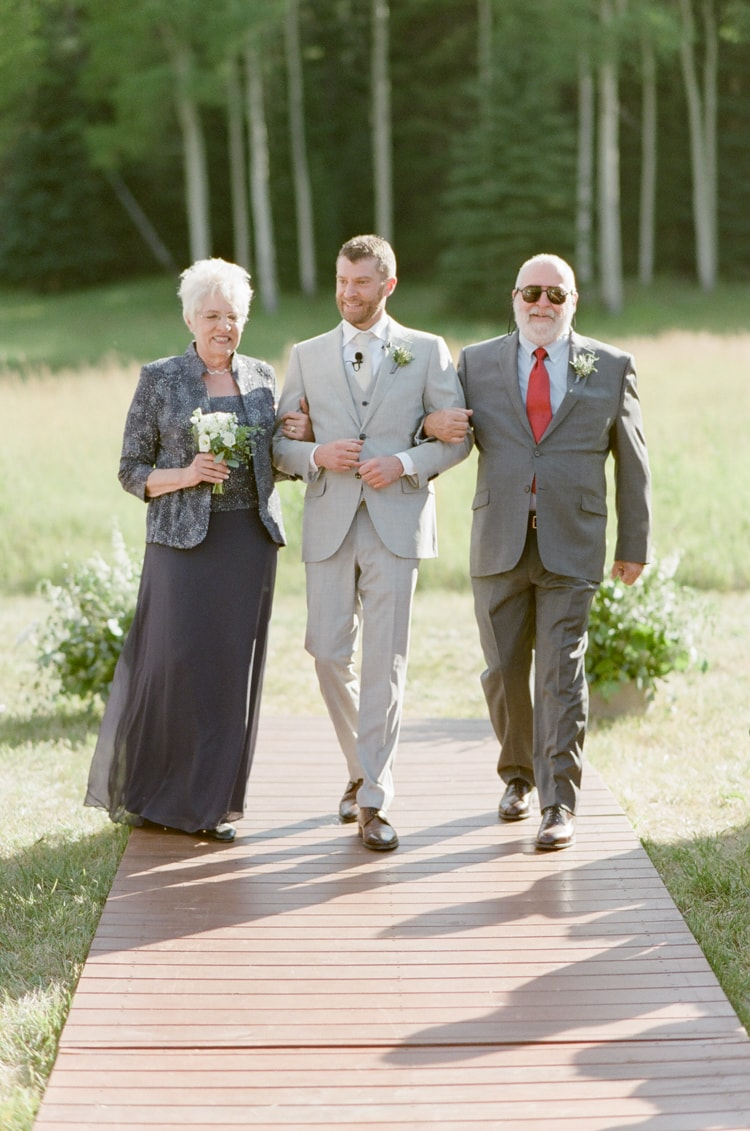 Groom and his parents walking down the aisle at Colorado wedding