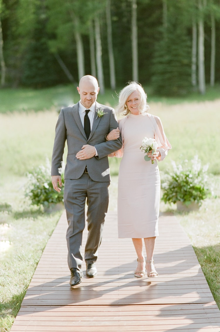 Mother of the bride and her son walking down the aisle at Vail wedding