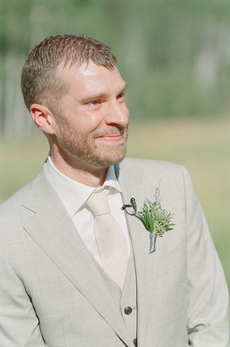 Groom smiling and crying when seeing his bride for the first time on wedding aisle