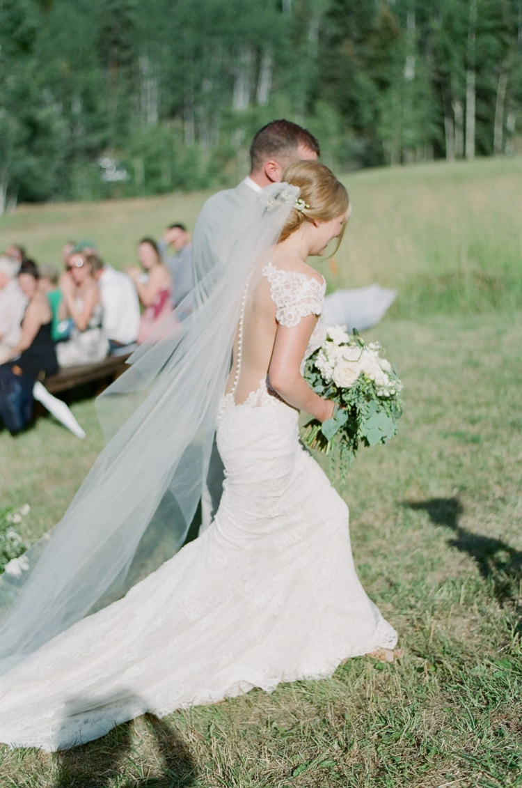 Bride and groom walking away from wedding aisle after saying 'I do'