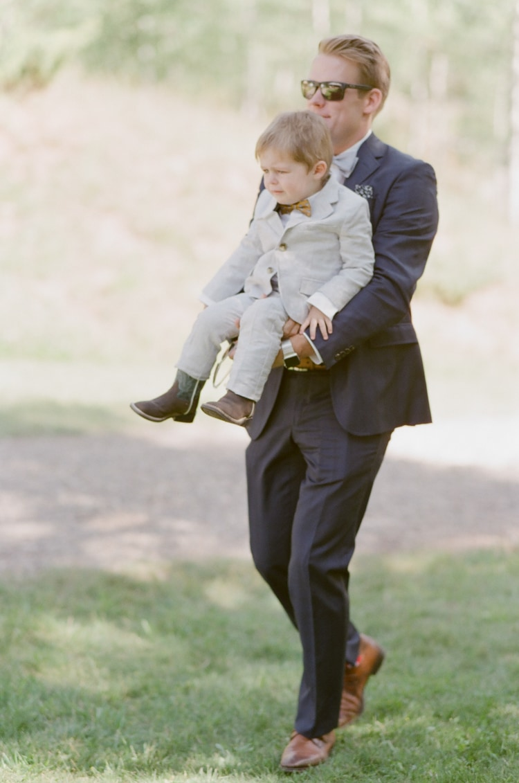 Wedding guest carrying ring bearer at Eaton Ranch