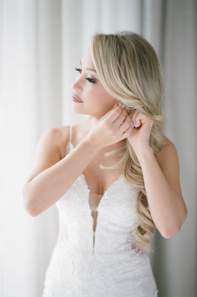Bride putting her earrings on in the wedding suite of Four Seasons Vail