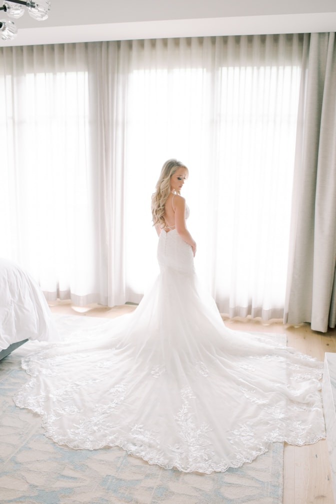 Bride in her gorgeous Essence of Australia dress with long train standing in front of window at Four Seasons Vail