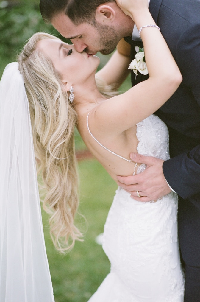 Bride and groom kissing each other under ceremony arch at Larkspur events and dining