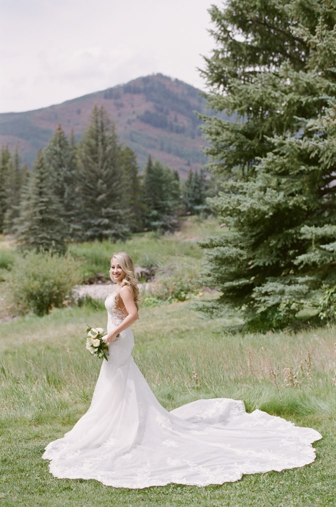 Bride standing in her Essence of Australia wedding dress in front of Vail mountains