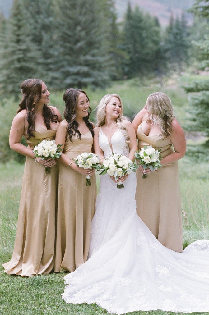 Bride standing with her bridesmaids in front of Vail mountain on her Vail wedding day