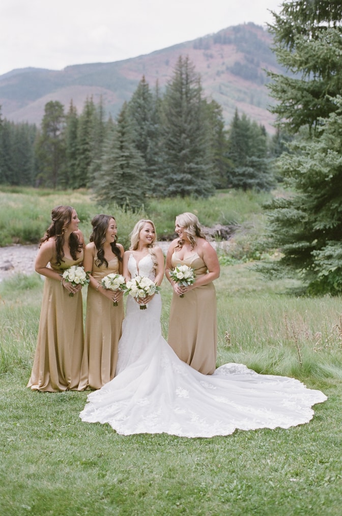 Bride and bridesmaids standing in front of Vail mountains for Vail wedding photographer Tamara Gruner