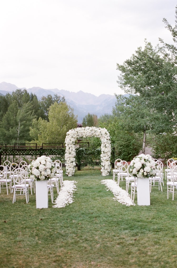 White floral ceremony arch at lLrkspur events and dining wedding in Vail