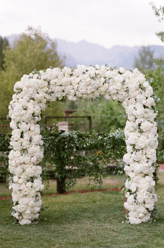 Larkspur events and dining wedding with white floral ceremony arch