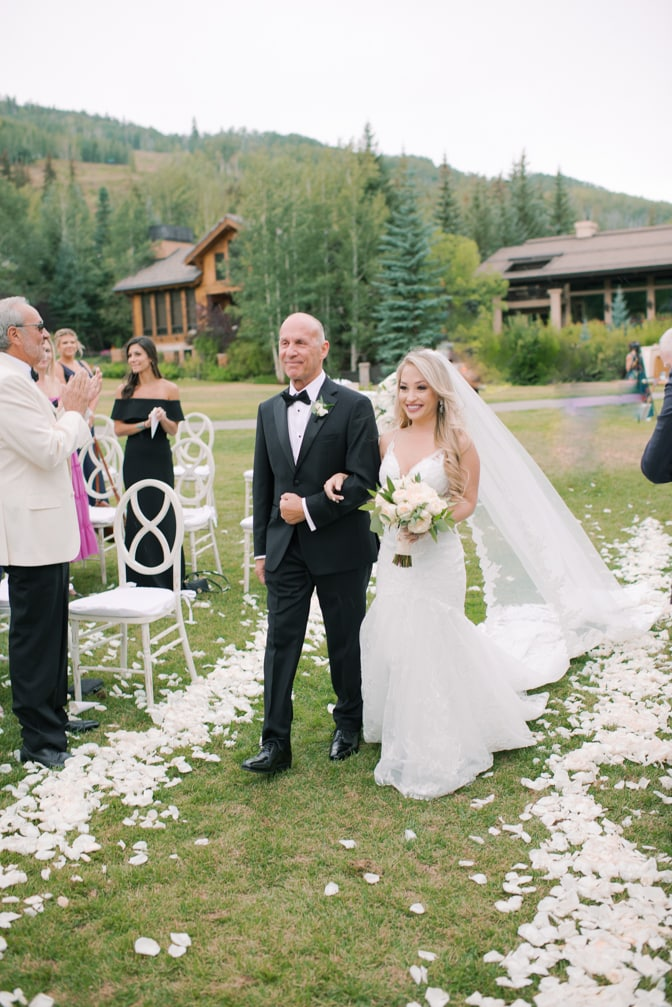 Bride walking down the aisle with her dad at Larkspur events and dining in Vail