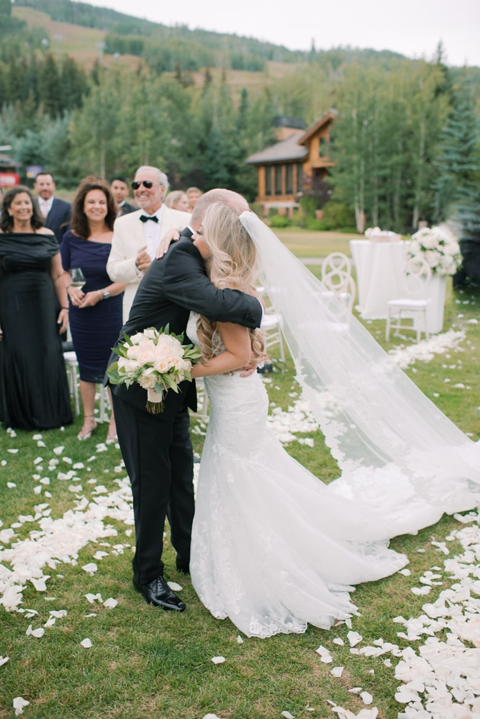 Bride embracing her dad after walking down the aisle at Larkspur events and dining in Vail