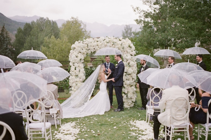 Bride and groom holding each others hand under the ceremony arch during their Vail wedding