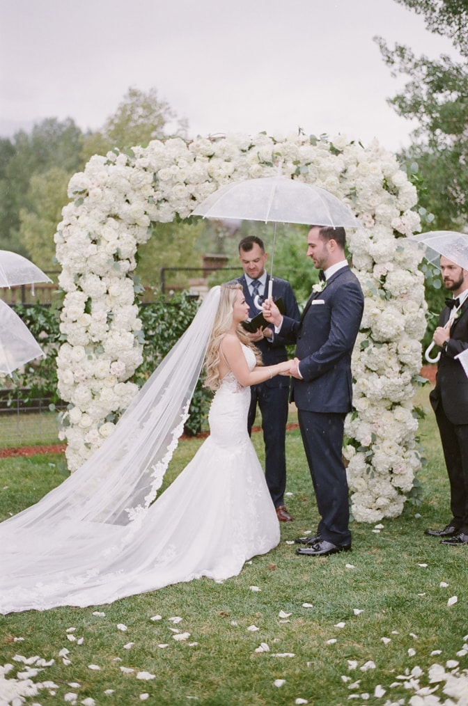 Bride and groom standing under ceremony arch at Larkspur events and dining wedding in Vail