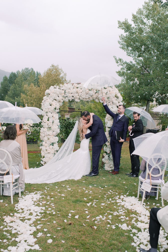 Bride and groom kissing each other under the ceremony arch during their Vail wedding at Larkspur events and dining