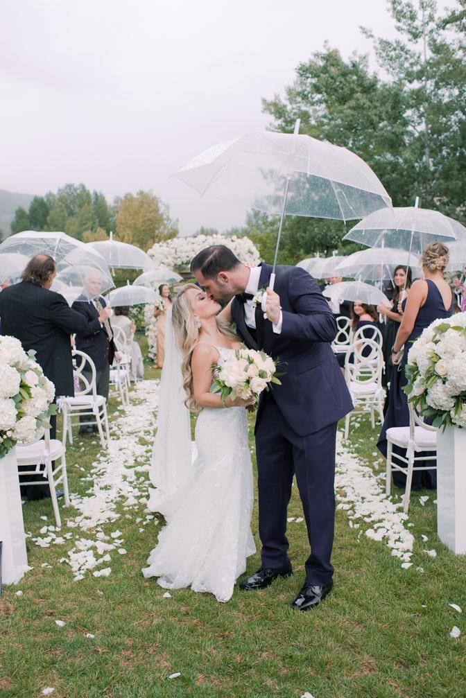 Bride and groom kissing each other under an umbrella after their Larkspur events and dining wedding in Vail