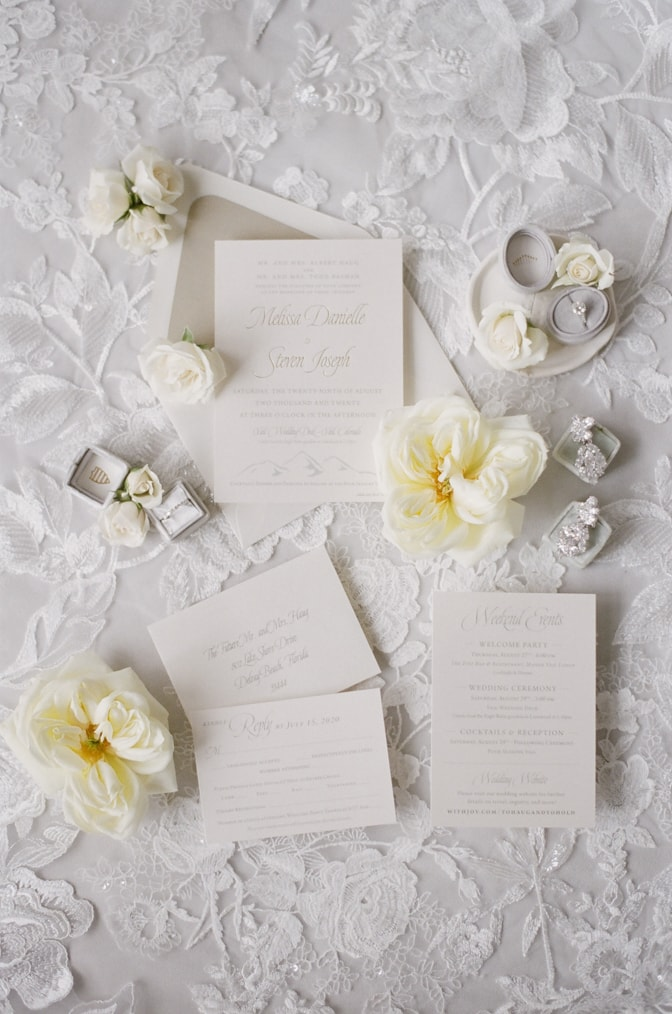 Wedding invitation placed on veil with floral decor at Four Seasons Vail