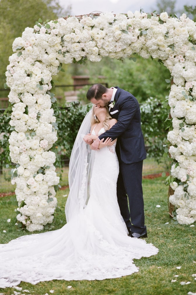 Bride and groom kissing under ceremony arch for Vail wedding photographer Tamara Gruner