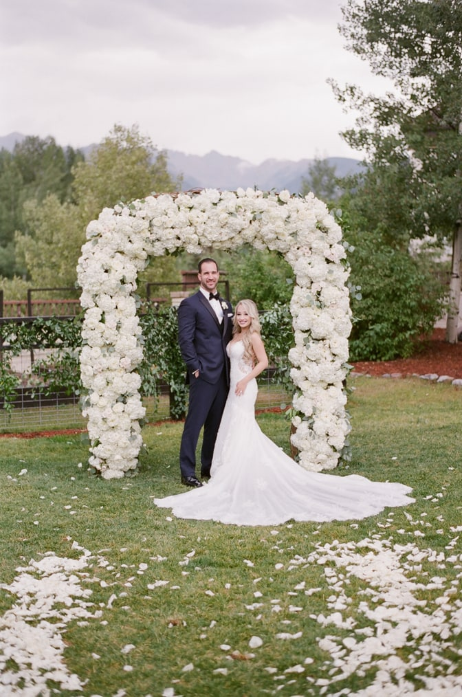 Bride and groom standing under white floral ceremony arch on their wedding day at Larkspur events and dining in Vail