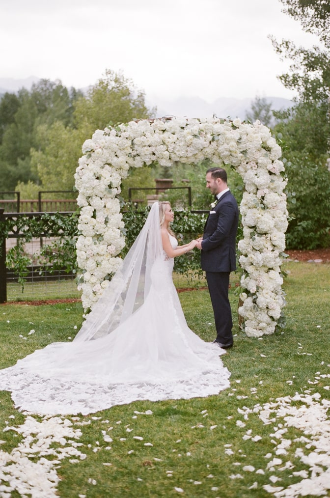 Bride and groom standing under white floral arch at Larkspur Events and Dining in Vail Colorado