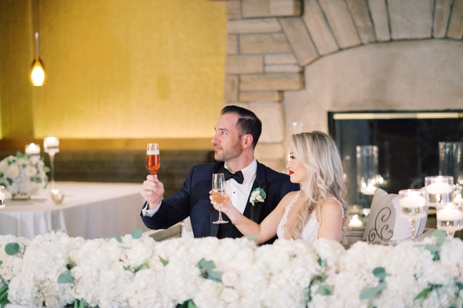 Bride and groom cheering with champagne during their wedding reception at Larkspur events and dining in Vail