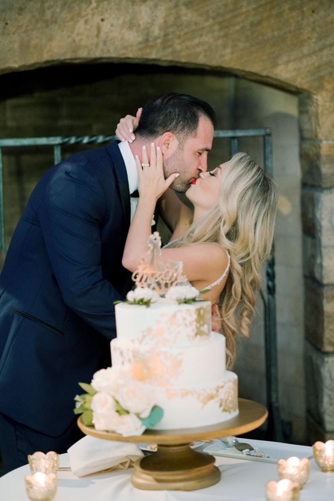 Bride and groom kissing each other after cutting wedding cake at their Vail wedding